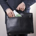 Businessman with a briefcase full of money in the hands of on gray background